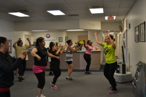 "Caption: Clinic patients and community members participate in Zumba a component of the Wellness Program.  ""Before Zumba, I could not keep up with my kids. Now I have lost 15 pounds and my knees feel better and I can run."""